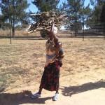 Африканска майка, носи дърва за огрев и малкото си, докато се разхожда